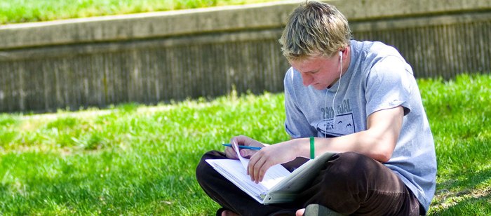Student studying outside the UMBC Commons facing the Quad